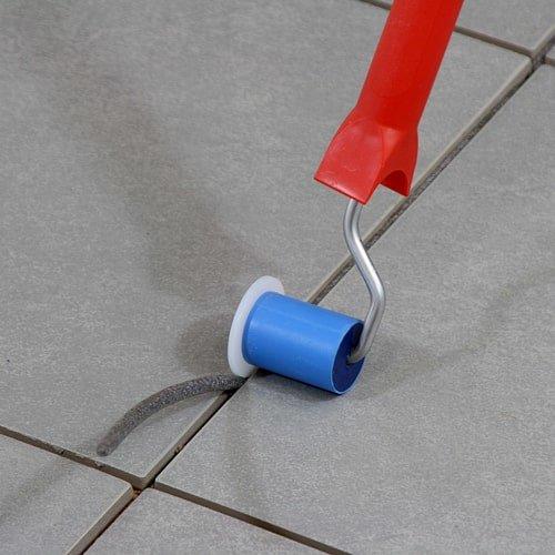 Rundprofil-Füllroller für PE-Rundprofile mit Handgriff. Blauer Roller mit rotem Griff. Rundprofil in graue Fliesen einbringen - KARL DAHM